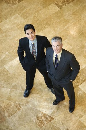 6455307: Two business men stand on a marble floor with hands in their pockets. They are looking up towards the camera. Vertical shot. Stock Photo