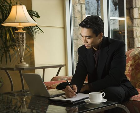 A young Asian businessman looking at a laptop computer whiles taking notes on a notebook. Horizontal shot. Stock Photo - 6455367