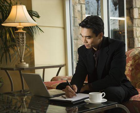 Eine asiatische Jungunternehmer Blick auf einem Laptop-Computer whiles wobei Notizen auf einem Notebook. Horizontal gedreht.