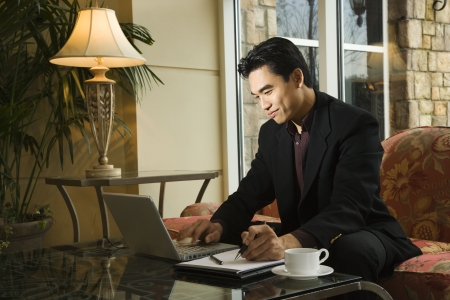lobby: A young Asian businessman typing on a laptop computer whiles taking notes on a notebook. Horizontal shot. Stock Photo