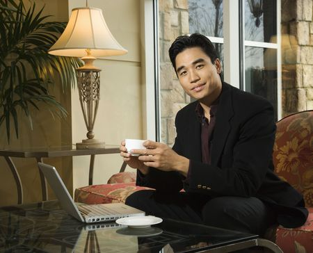 A young Asian businessman holds a coffee cup while seated at his laptop. Horizontal shot. photo