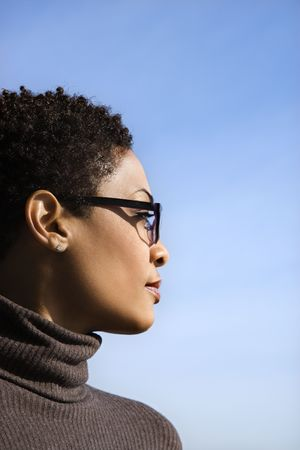 Attractive African American woman looks to the side against a blue sky background. Vertical shot.