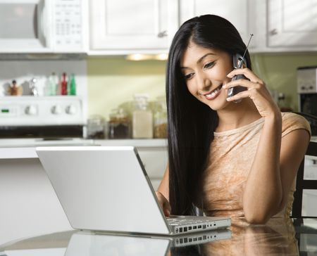 A young woman chats on her mobile phone while sitting at the kitchen table in front of a laptop.  Horizontal shot. Stock Photo