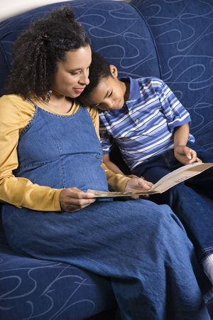 A mid adult woman sitting on a couch reading a book to her young son. Vertical shot. photo