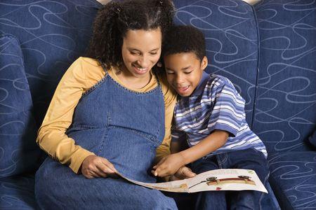 Eine Mitte erwachsene Frau, die auf eine Couch, ein Buch zu lesen, um ihre jungen Sohn sitzen. Horizontal gedreht.