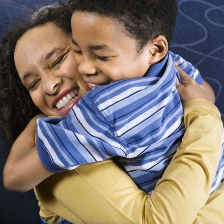 A mid adult African American woman affectionately hugs her young son. Square shot. Stock Photo
