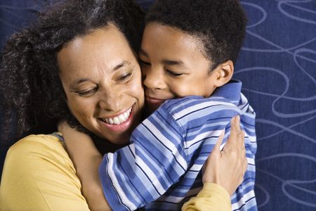 A mid adult African American woman affectionately hugging her young son. Horizontal shot. photo