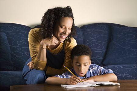 Eine Mitte Erwachsene afroamerikanische Frau auf eine Couch sitzt und hilft dabei, Ihre junge einige mit seine Hausaufgaben. Horizontal gedreht.