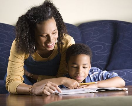 A mid adult African American woman sits on a couch while helping her young some with his homework. Horizontal shot.