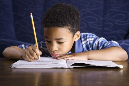 writing black: Young African American boy sitting on the floor in front of a coffee table doing homework. Horizontal shot.
