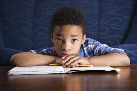 one room school house: Young African American boy sits on the floor at a coffee table. He is looking towards the camera with his homework on the table. Horizontal shot.