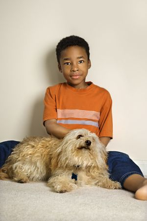 black carpet: Portrait of a young African American boy sitting on the floor and petting a small dog. Vertical shot.  Stock Photo