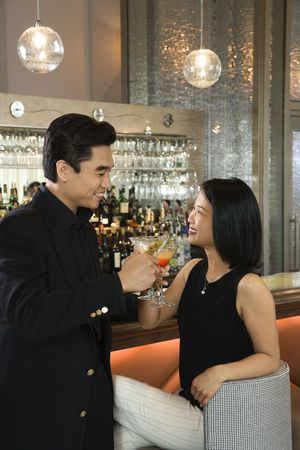 Attractive Asian man and woman toasting with their cocktails while at a bar. Vertical shot.