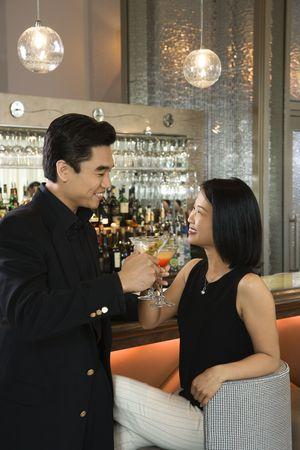 Attraktive asiatischen Mann und Frau, die Toastungsgraden mit ihren Cocktails und gleichzeitig eine Bar. Vertikale erschossen.