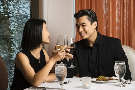 up date: Attractive young Asian couple toast their wine at a restaurant table. Horizontal shot.