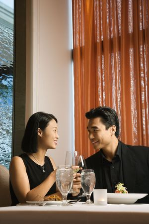 up date: Attractive young Asian couple sit at a restaurant table smiling and toasting their wine. Vertical shot.