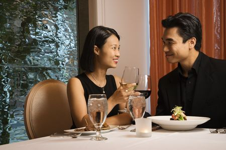Attractive young Asian couple sit at a restaurant table smiling and toasting. Horizontal shot. Stock Photo