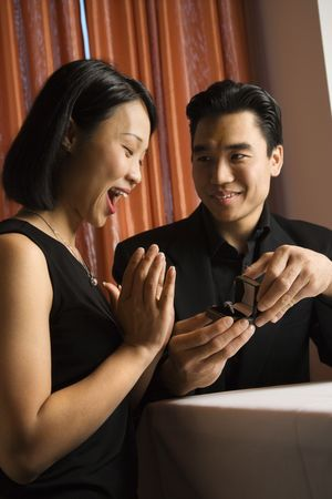Attractive young Asian man proposes to an attractive Asian woman with an engagement ring. Vertical shot. photo