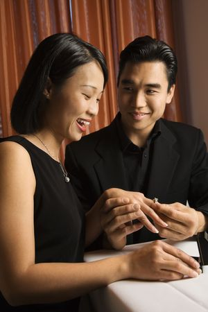 Attractive young Asian man places an engagement ring on an attractive young Asian woman. Vertical shot. photo