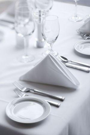 tavolo da pranzo: Posizionare le impostazioni su un bianco, elegante tavolo da pranzo in un ristorante. Girato verticale.  Archivio Fotografico
