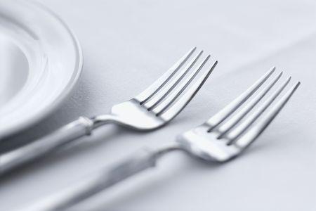 tavolo da pranzo: Due forchette seduta side-by-side su un tavolo da pranzo con tovaglia bianca. Tiro orizzontale.