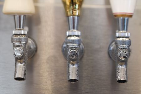 three objects: Three beer tap spouts with condensation showing on the openings. Horizontal shot. Stock Photo