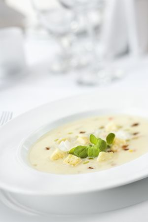 chowder: Bowl of gourmet soup elegantly displayed with garnish in a restaurant. Vertical shot.