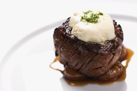 Beef filet dinner entree with garnish and brown sauce displayed on a white dinner plate. Horizontal shot. Stock Photo - 6395885