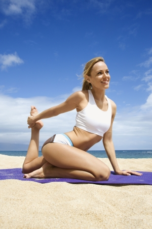 Attractive young woman practices yoga on a sandy beach. The ocean can be seen in the distance. Vertical shot.