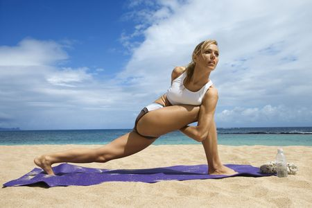 twist: Attractive young woman stretches while doing yoga. She is on a sandy beach with the ocean in the background. Horizontal shot. Stock Photo
