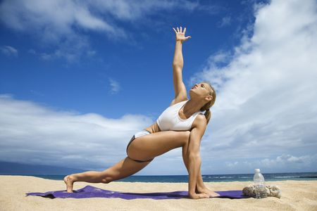 Attractive young woman extends an arm while and doing yoga on beach with the ocean in the background. Horizontal shot.