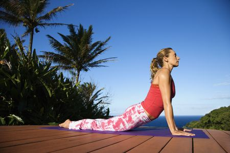 holistic view: Attractive young woman in red practices yoga on a deck with the ocean in the background. Vertical shot.