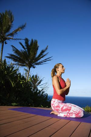 holistic view: Attractive young woman in red sits on an exercise mat doing yoga with the ocean in the background. Vertical shot.