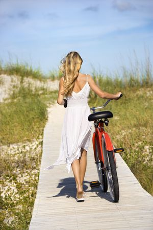 looking away from camera: Rear view of young female as she walks her bike down a boardwalk. Vertical shot. Stock Photo