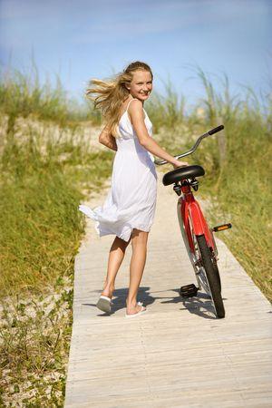 well dressed girl: Young teen female smiles back as she walks her bike down a boardwalk. Vertical shot.