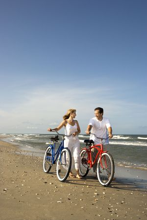 Smiling man and woman walk bicycles down the beach coast. Vertical shot. Stock Photo