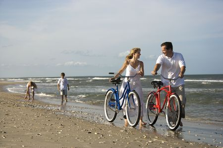 Husband and wife walk their bikes down the beach with children in the background. Horizontal shot. photo