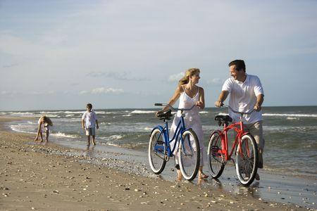 Mann und Frau Fuß Ihre Fahrräder unten am Strand mit Kindern im Hintergrund. Horizontale erschossen.
