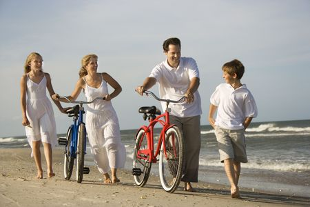 Family walks down the beach as mother and father push their bicycles. Horizontal shot. Stock Photo