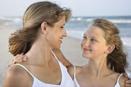 looking away from camera: Mother and daughter smile with arms around one another. Horizontal shot. Stock Photo