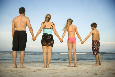 Rear view of a family holding hands at the beach. Horizontal shot. photo