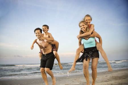 Mother and father give their children piggy back rides at the beach. Horizontal shot. Stock Photo