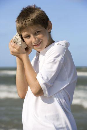 Boy listens to a shell at the beach. Vertical shot. photo