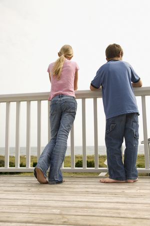 boy barefoot: Boy and girl look over a porch railing at the beach. Vertical shot. Stock Photo