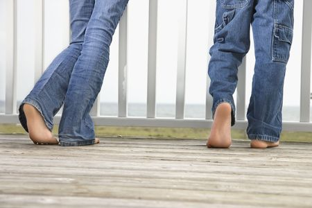 boy barefoot: Rear view of brother and sisters legs as they stand on on the boardwalk. Horizontal shot. Stock Photo