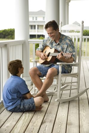 Man playing guitar as a boy listens on the front porch of his home. Vertical shot. photo