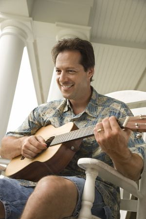 Man plays guitar while sitting in a rocking chair on a porch. Vertical shot. Stock Photo - 6455324
