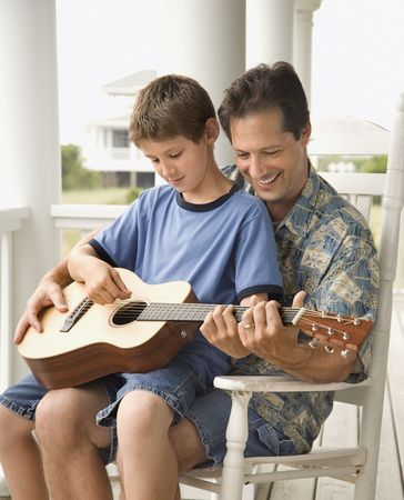 Son sits on his fathers lap while playing guitar. Vertical shot. Stock Photo