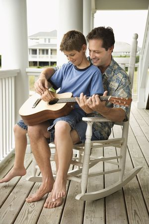 on lap: Son sits on his fathers lap while playing guitar. Vertical shot. Stock Photo
