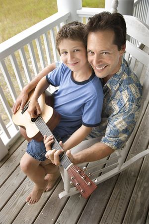 Boy playing guitar while sitting on his father's lap. Vertical shot. Stock Photo - 6455329